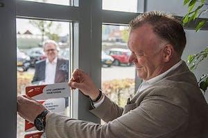 Abemec directeur Hans Quint plakt de erkenningssticker op het raam, onder toeziend oog van Ab van Ravestein, algemeen directeur van de RDW.