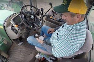 Boer checkt zijn smartphone terwijl zijn tractor gedeeltelijk autonoom rijdt dankzij AgJunction autosteer. - Foto: Still uit AgJunction-video